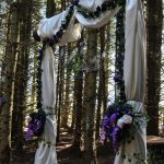 magnificent 3m high solid log arch with drapes and flower adorned ropes and bouquet in our woodland cathedral