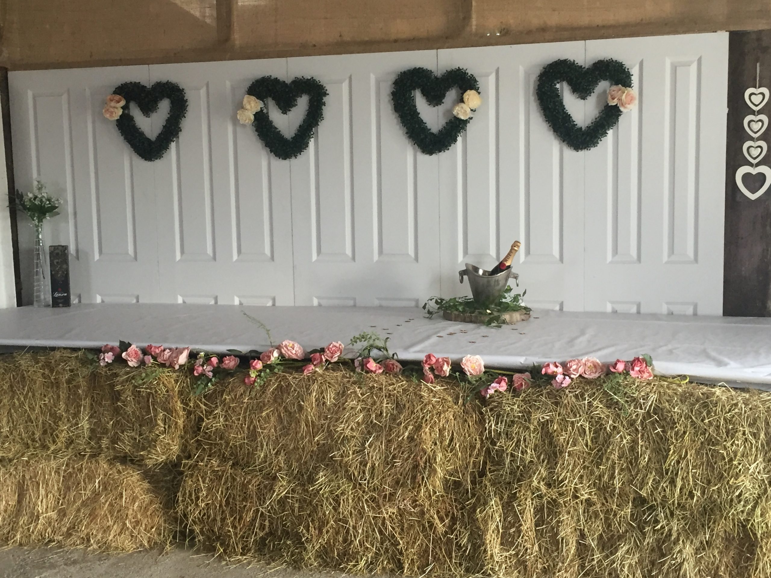 beautifully decororated banquette table festooned with pink flowers and hearts