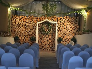 solid log wall backdrop for wedding ceremony